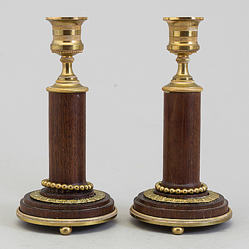 A pair of 20th century mahogany and brass candlesticks.