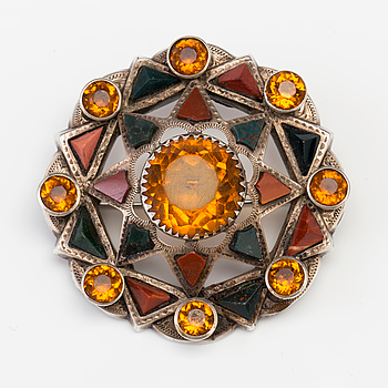 A BROOCH set with amber-coloured paste, heliotrope and jasper.