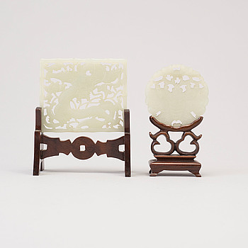 Two carved Chinese nephrite sculptures on wooden stands, 20th century.