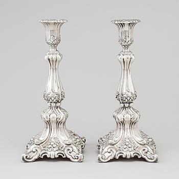 A pair circa 1900 silver of rococo style candle sticks.