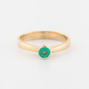 A faceted emerald ring.