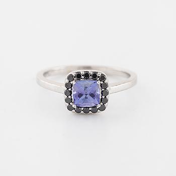 RING, med tanzanit ca 0.70 ct samt briljantslipade svarta diamanter totalt ca 0.25 ct.