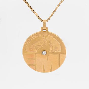 """HÄNGSMYCKE på kedja, 18K guld + 1 briljant ca 0.03 ct, rund plakett med """"EMI""""-emblem."""