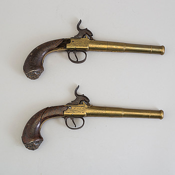 A secon half of the 19th century pair of Queen Anne brass percussion pistols converted from flintlock by Brueton, London.