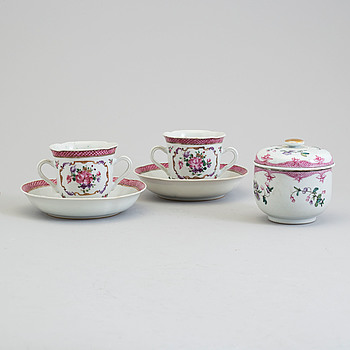 A pair of famille rose cup with stands and a sugar bowl with cover, Qing dynasty, Qianlong (1736-95).