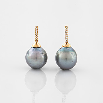 A pair of cultured Tahiti pearl and brilliant cut diamond earrings.