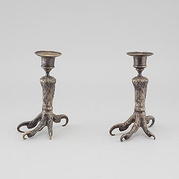 A pair of silvered metal candlesticks, around the year 1900.
