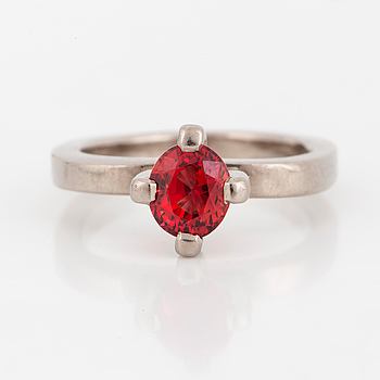 A mixed-cut orangered sapphire ring.