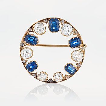 1012. A brooch in 14K gold set with old- and rose-cut diamonds and faceted sapphires.