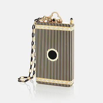 A Cartier Art Deco Vanity Case/Minaudière in 18K gold, black enamel and onyx. on the inside a mirror, a separate compartment with lid, a...
