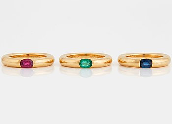 "1015. Three Cartier ""Ellipse"" rings in 18K gold set with a faceted  sapphire, an emerald and a ruby."