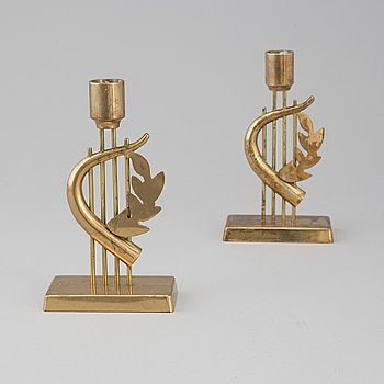 "A pair of brass candle sticks ""Design G Magnusson 1988""."