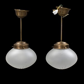 A pair of contemporary brass and glass ceiling lamps.
