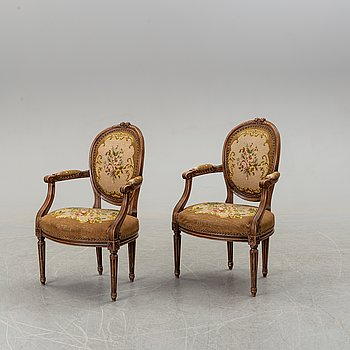 A pair of Louis XVI-style walnut armchairs circa 1900.