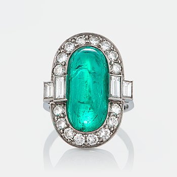 1039. A platinum ring set with a cabochon-cut emerald ca 7 cts and brilliant and baguette-cut diamonds.