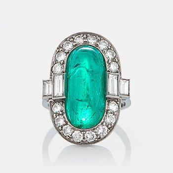 1039. Ring med en caboconslipad smaragd ca 7 ct samt briljant- och baguetteslipade diamanter ca 1 ct.