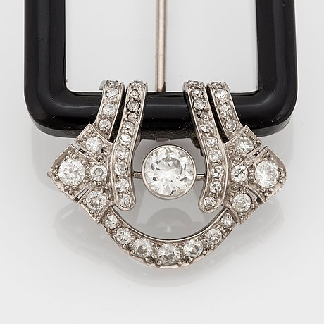 A janesich art deco brooch in onyx and platinum set with old- and eight-cut diamonds.