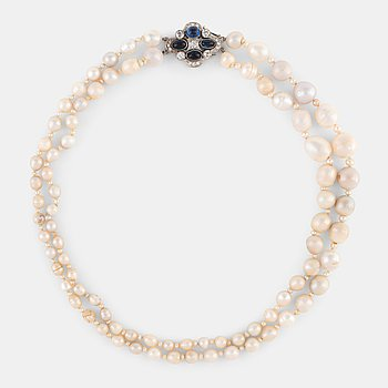 A two strand natural pearl-necklace Ø 4.10-10 mm with smaller pearls between.