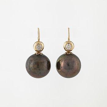 A pair of cultured Tahiti pearla nd brilliant cut diamond earings.