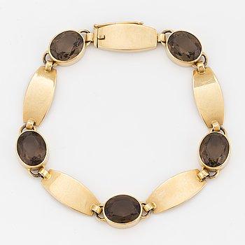 A Just Andersen 18K gold and smoky quartz bracelet.
