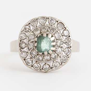 A ring set with a faceted emerald and eight-cut diamonds.