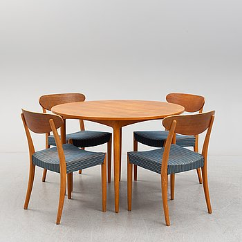 A 1960's teak dining set with four chairs and a table with 2 additional leaves.