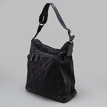 BURBERRY, a black nylon and leather nursing bag.
