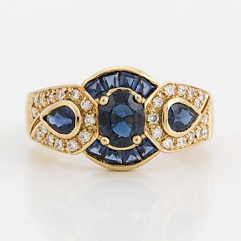 An 18K gold ring with sapphire and brilliant-cut diamonds.