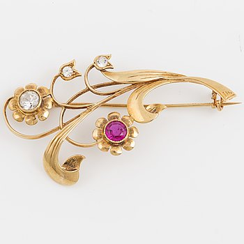 An 18K gold flower brooch set with white stones and a red stone.