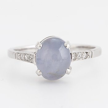 A cabochon-cut star sapphire and diamond ring.