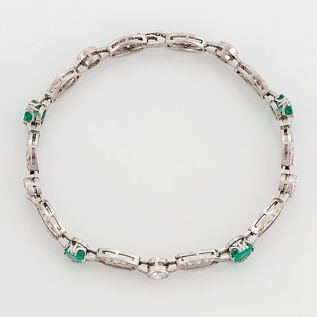 An 18k white gold bracelet set with faceted emeralds.