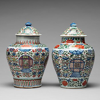 570. A matched pair of Transitional wucai baluster vases with covers, 17th Century.