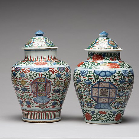 A matched pair of transitional wucai baluster vases with covers, 17th century.