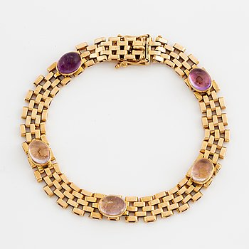 An 18K gold and cabochon-cut amethyst.