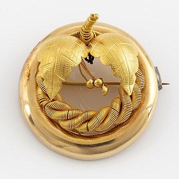 An 18K gold brooch.