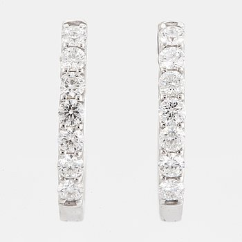 A pair of earrings set with round brilliant-cut diamonds.