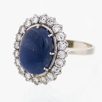 A RING, cabochon cut star sapphire, brilliant cut diamonds, 18K white gold.