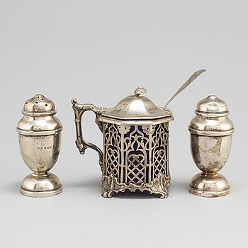 A silver mustard jug and two shakers, England.