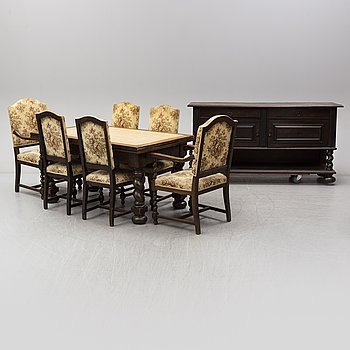 A barock style dining table with 10 chairs and a sideboard. First half of the 20th century.