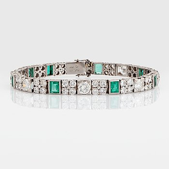 A platinum bracelet set with round brilliant- and old-cut diamonds and faceted emeralds.