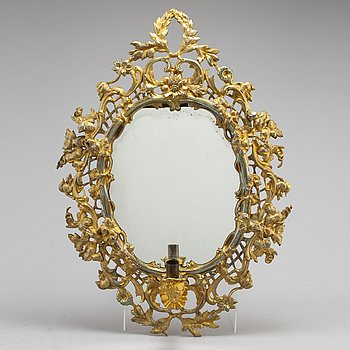 A 19th century brass rococo style mirror with candleholder.