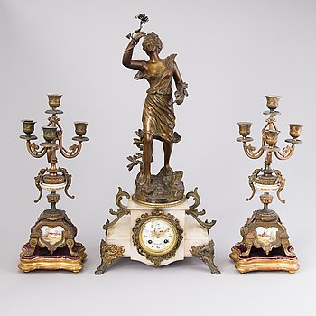 A Central European mantel clock and a pair of candelabra from around the turn of the 20th Century.