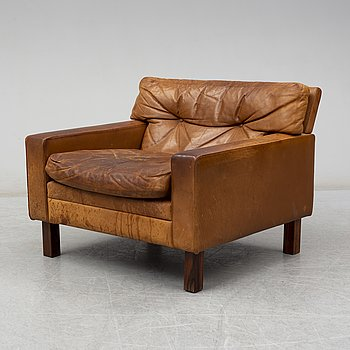 A 1960's/1970's leather covered easy chair with rosewood legs.