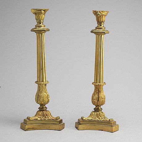 A pair of late 19th century empire-style bronze candlesticks.