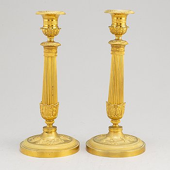 A pair of first half of the 19th century Empire candel sticks, gilded bronze, first half of the 19th century.