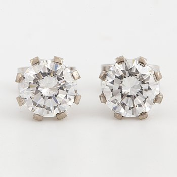 Brilliant-cut diamond solitaire earrings.
