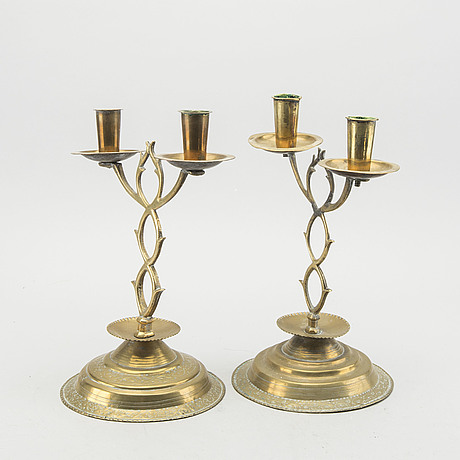A pair of brass candelabras dated 1810 and 1812