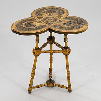 A wooden table from around 1900, cut decor.