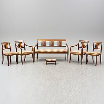 A set of two armchairs, four chairs, a sofa and a stool, in 8 parts. Empire-style, ca 1900.
