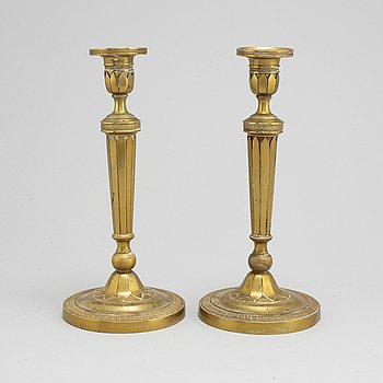A pair of late 19th century Empire style brass candlesticks.